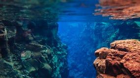 L'eau glaciaire clair comme de l'eau de roche bleue en parc national Islande de Silfra Thingvellir photos stock