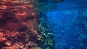 L'eau glaciaire clair comme de l'eau de roche bleue en parc national Islande de Silfra Thingvellir photographie stock libre de droits