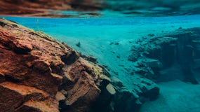 L'eau glaciaire clair comme de l'eau de roche bleue en parc national Islande de Silfra Thingvellir photographie stock