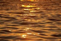 L'eau lisse en mer dans les rayons du coucher du soleil photos libres de droits