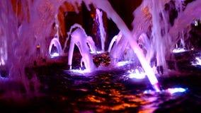 L'eau lumineuse dans la fontaine de ville la nuit banque de vidéos