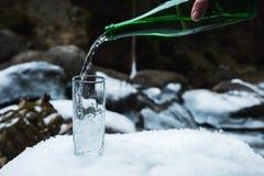 L'eau minérale minérale est versée d'une bouteille verte en verre dans un becher en verre clair image libre de droits