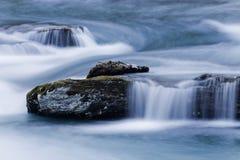 L'eau molle au-dessus des pierres dans le courant bleu de rivière Image stock