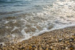 L'eau mousseuse de plage rencontre la plage rocheuse photos libres de droits