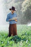 L'eau numérique de système d'arrosage de chapeau de technologie de plantation de tablette de contrôle de travailleur du soleil d' photographie stock libre de droits