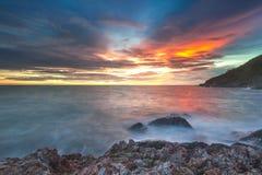 L'eau orange-clair d'impact de coucher du soleil sur la plage Image libre de droits