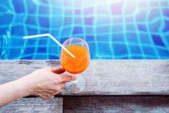 l'eau orange d'été de glace de boissons de citron de carafe Femme détendant à la piscine dans son Vacatio image libre de droits