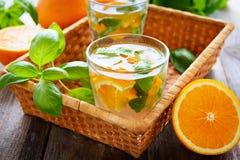 L'eau orange faite maison avec le basilic images stock