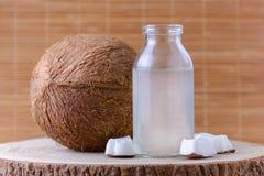 L'eau organique de noix de coco dans un pot et une noix de coco en verre sur le fond naturel photos stock