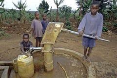 L'eau ougandaise d'effort d'enfants à la pompe à eau Photographie stock