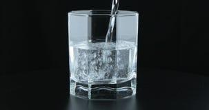 L'eau pétillante froide fraîche de versement dans le verre à boire banque de vidéos