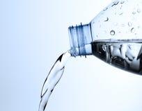 L'eau pleuvante à torrents d'une bouteille Photographie stock libre de droits