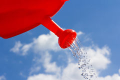L'eau pleuvante à torrents de bidon d'arrosage contre le ciel Photographie stock