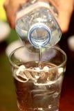 L'eau pleuvante à torrents de la bouteille Image stock