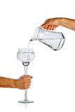 L'eau pleuvante à torrents de main de la cruche en verre Photos stock