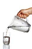 L'eau pleuvante à torrents de main de la cruche en verre Images stock