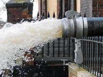 L'eau pompée par le tuyau photographie stock