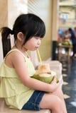 L'eau potable de noix de coco de fille mignonne Images stock