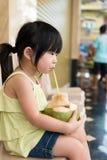 L'eau potable de noix de coco de fille mignonne Photo stock