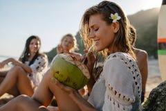 L'eau potable de noix de coco de femme attirante avec des amis Photographie stock