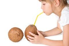 L'eau potable de noix de coco de petite fille Photos stock