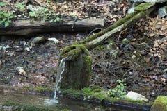 L'eau pure n débordant se laissant tomber du tuyau en bois photo libre de droits