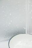 L'eau pure tombant dans une tasse blanche Images stock