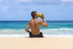 L'eau régénératrice de noix de coco par la mer Images libres de droits
