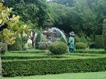 L'eau remplissante de jardinier dans la fontaine dans le sumner en parc vert tropical Image libre de droits
