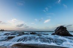 L'eau rushiing au-dessus de la roche sur la plage coquillière Photos stock
