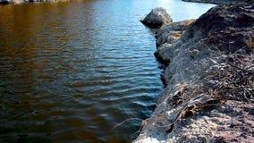 L'eau sale circulant calmement sur la vue à angles supérieure de moment de bord de mer rocheux de sable banque de vidéos
