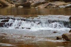 L'eau se précipitant au-dessus des roches Image stock