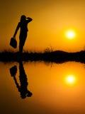 L'eau se reflètent de la femme d'affaires tenant et tenant le sac aux soleils Photo libre de droits