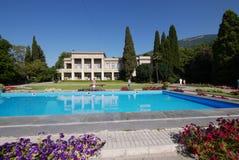 L'eau transparente de piscine avec l'élevage fleurit le long des bords situés dans le parc à côté d'une belle maison contre Photos stock