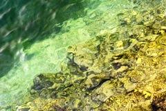 L'eau transparente verte et jaune Photographie stock libre de droits