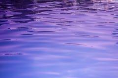 L'eau ultra-violette de la piscine ou de la mer avec des vagues et la lumière du soleil brille à la surface image stock