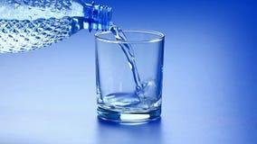 L'eau versant de la bouteille en plastique