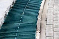 L'eau verte de drain de plancher en acier près de la route bétonnée photos libres de droits