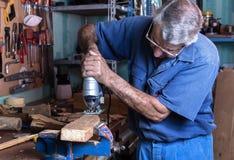 L'ebanista che lavora con il legno ha visto nel banco da lavoro in garage a Fotografie Stock Libere da Diritti