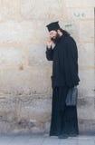 L'ecclésiastique se tient et parle à son téléphone portable dans la vieille ville de Jérusalem, Israël photographie stock libre de droits