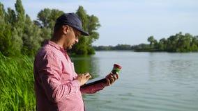 L'ecologo dello scienziato esamina il campione delle alghe verdi e digita i dati sulla compressa video d archivio