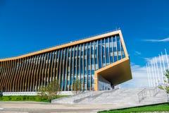 L'edificio per uffici nel prato con le finestre di vetro che riflettono le nuvole di galleggiamento, lungo la costruzione là è la Fotografia Stock