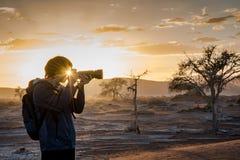 L'effetto di Sunstars attraverso il fotografo maschio osserva in sunris di mattina fotografie stock