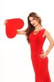L'efficace giovane donna in un vestito rosso con cuore rosso Valentin Immagine Stock