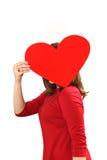 L'efficace giovane donna in un vestito rosso con cuore rosso Valentin Immagini Stock