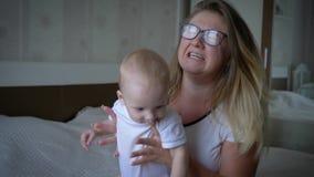 L'effort, mère nerveuse dans des lunettes soulève souvent le nourrisson dans des mains se reposant sur le lit banque de vidéos