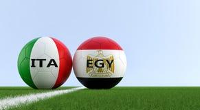 L'Egitto contro Partita di calcio dell'Italia - palloni da calcio nei colori nazionali di Egypts e di Italys su un campo di calci Immagini Stock