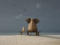 L'elefante ed il cane si siedono su una spiaggia Immagine Stock Libera da Diritti