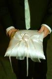 L'elemento portante di anello tiene il cuscino alla cerimonia nuziale fotografia stock libera da diritti