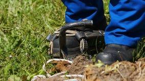 L'elettricista del movimento lento decolla i ferri di scalata su erba verde stock footage